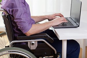 Disabled sitting at a desk and working on laptop